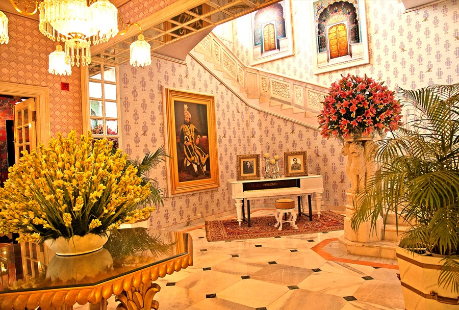 Theere is a grand piano and lots of paintings along the staricase of the palace